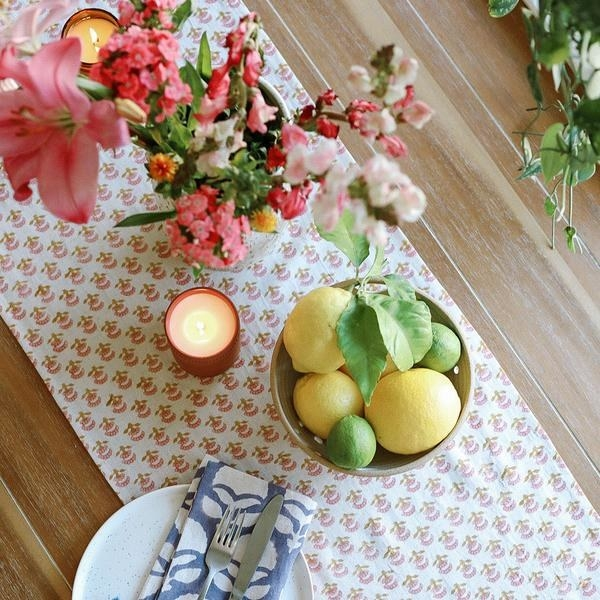 the table runner with a pink floral pattern on a wooden table covered with candles and a lemon bowl