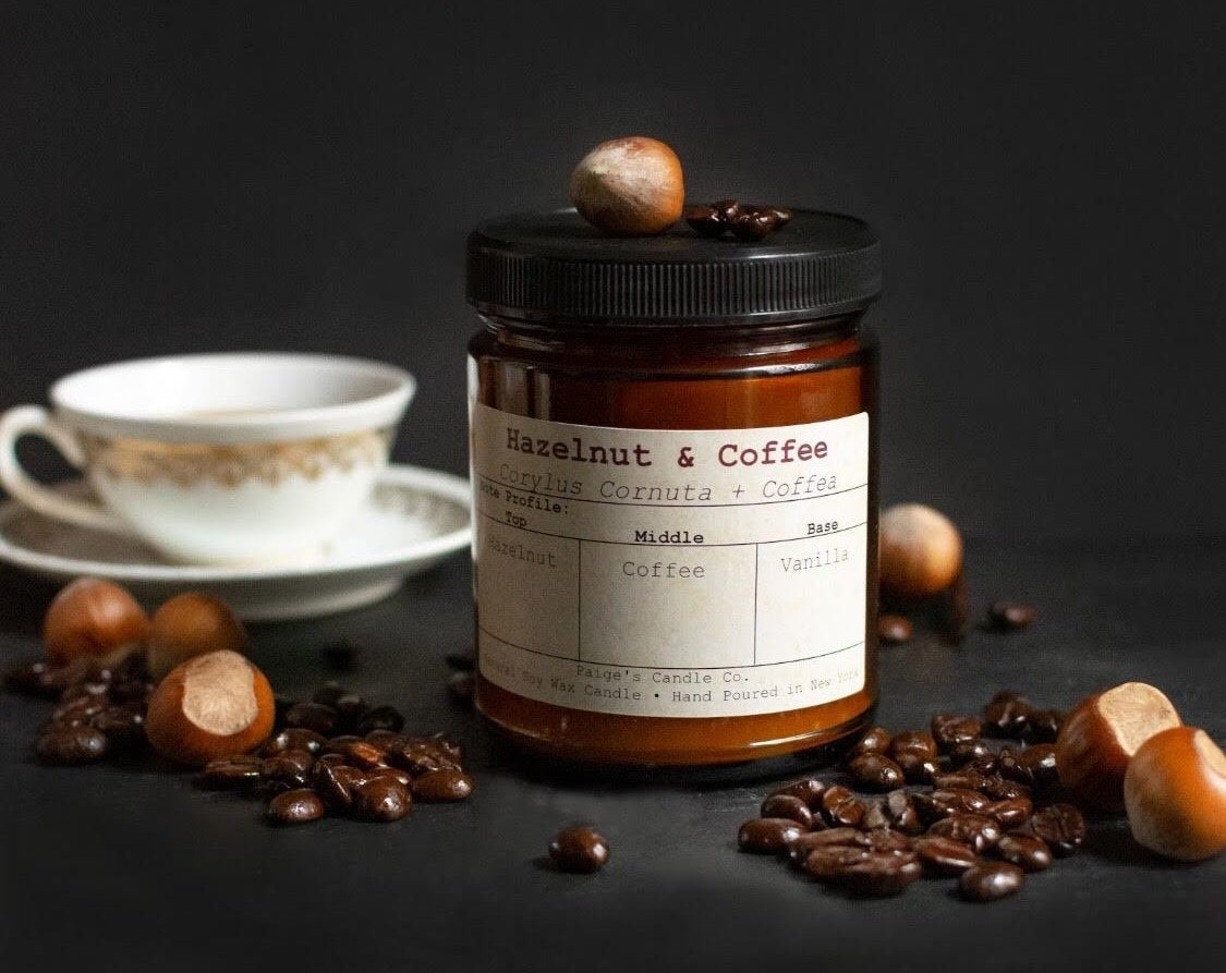"the amber-colored glass candle with black lid and the words ""hazelnut & coffee"" on the tan label"