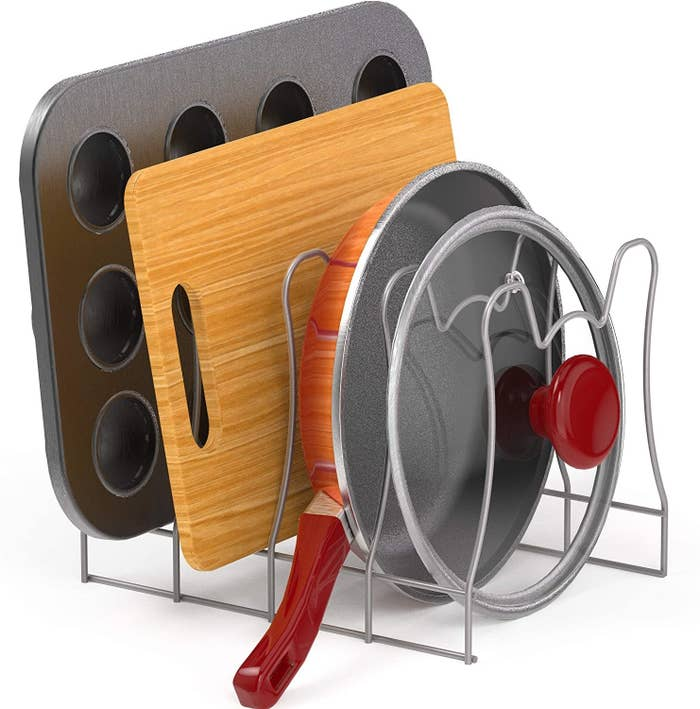 four slot wire rack with muffin pan, cutting board, skillet, and skillet lid stacked in their respective slots