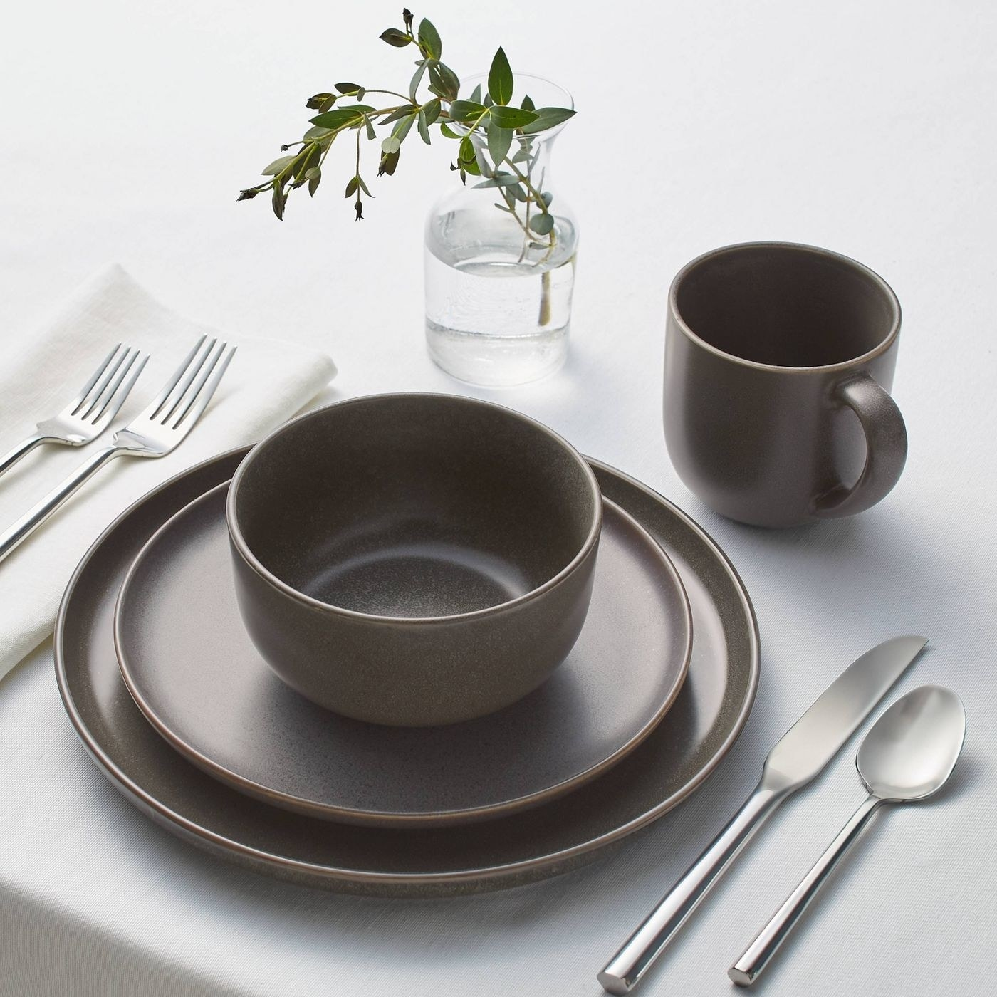 black and gold dinnerware set with two plates a bowl and a mug