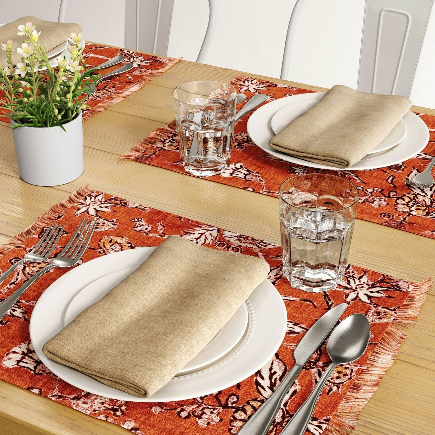 orange floral placemats with silverware and dinnerware on it