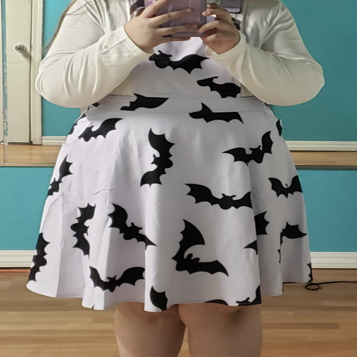 plus size reviewer wearing the white pinafore with a bat print on it