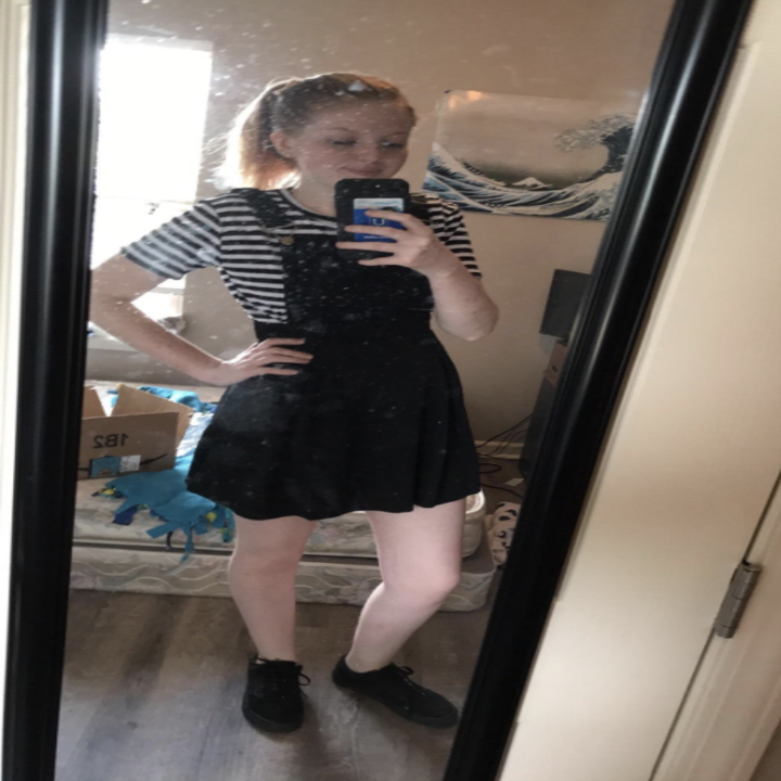 petite reviewer wearing the black dress with a striped shirt undereneath