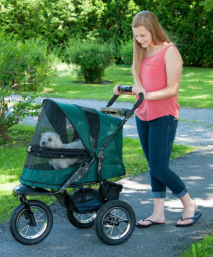 A model pushes the green stroller on a gravel path