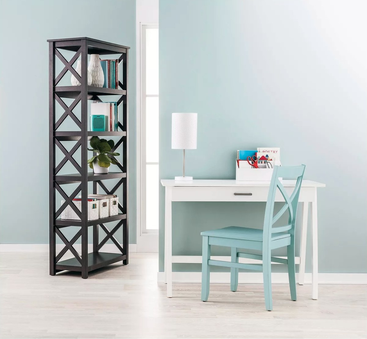 The wood writing desk in white with a large drawer next to a blue chair