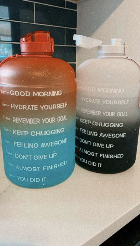 two water bottles that have markers on the side with motivational messaging to inspire you to drink water throughout the day