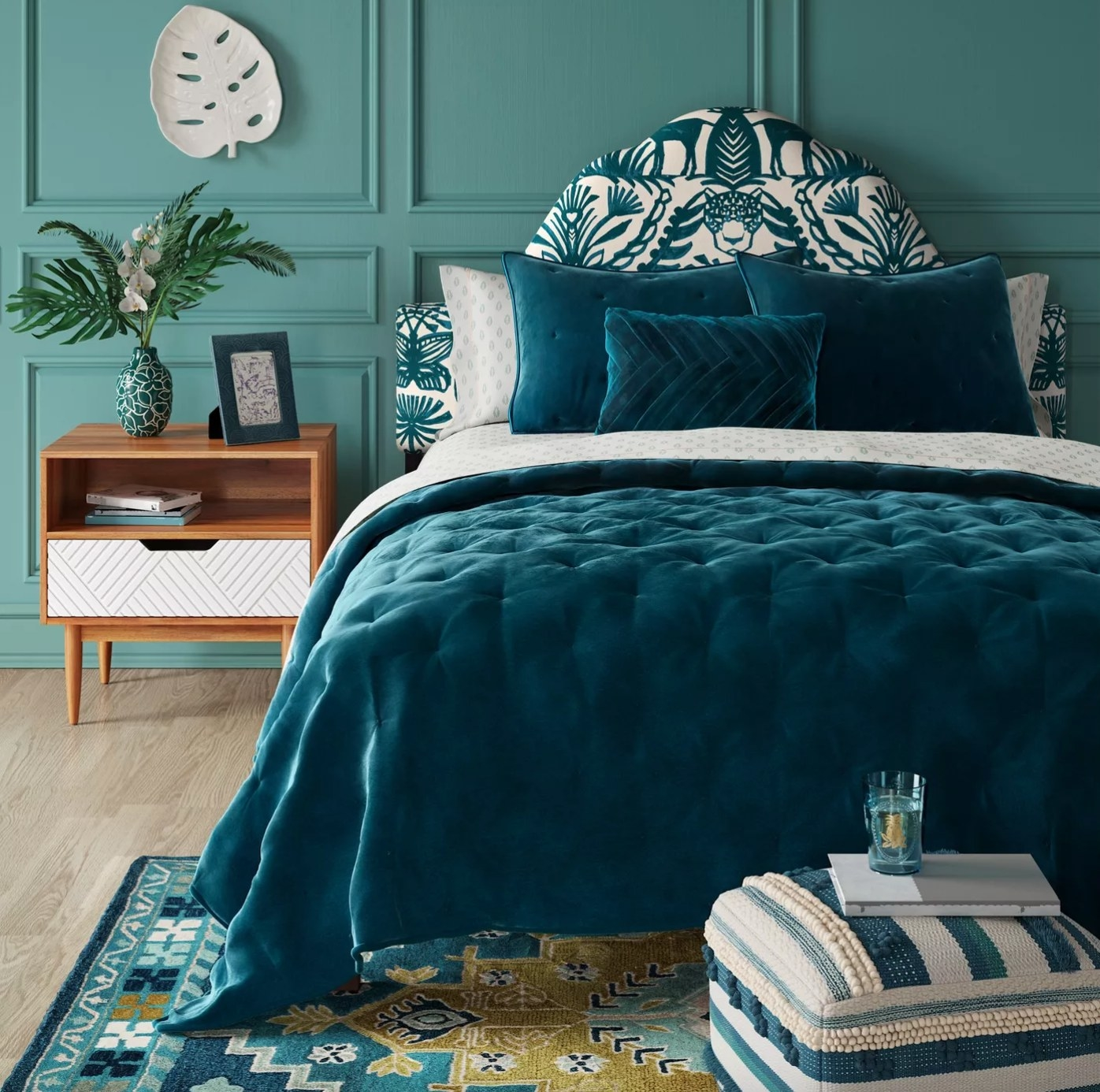 The midcentury modern nightstand in wood with a white drawer next to a bed with blue bedding