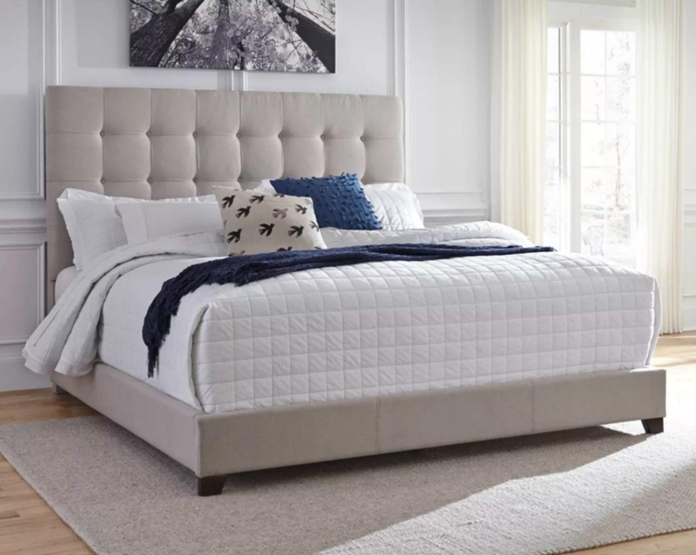 The upholstered bed frame in beige