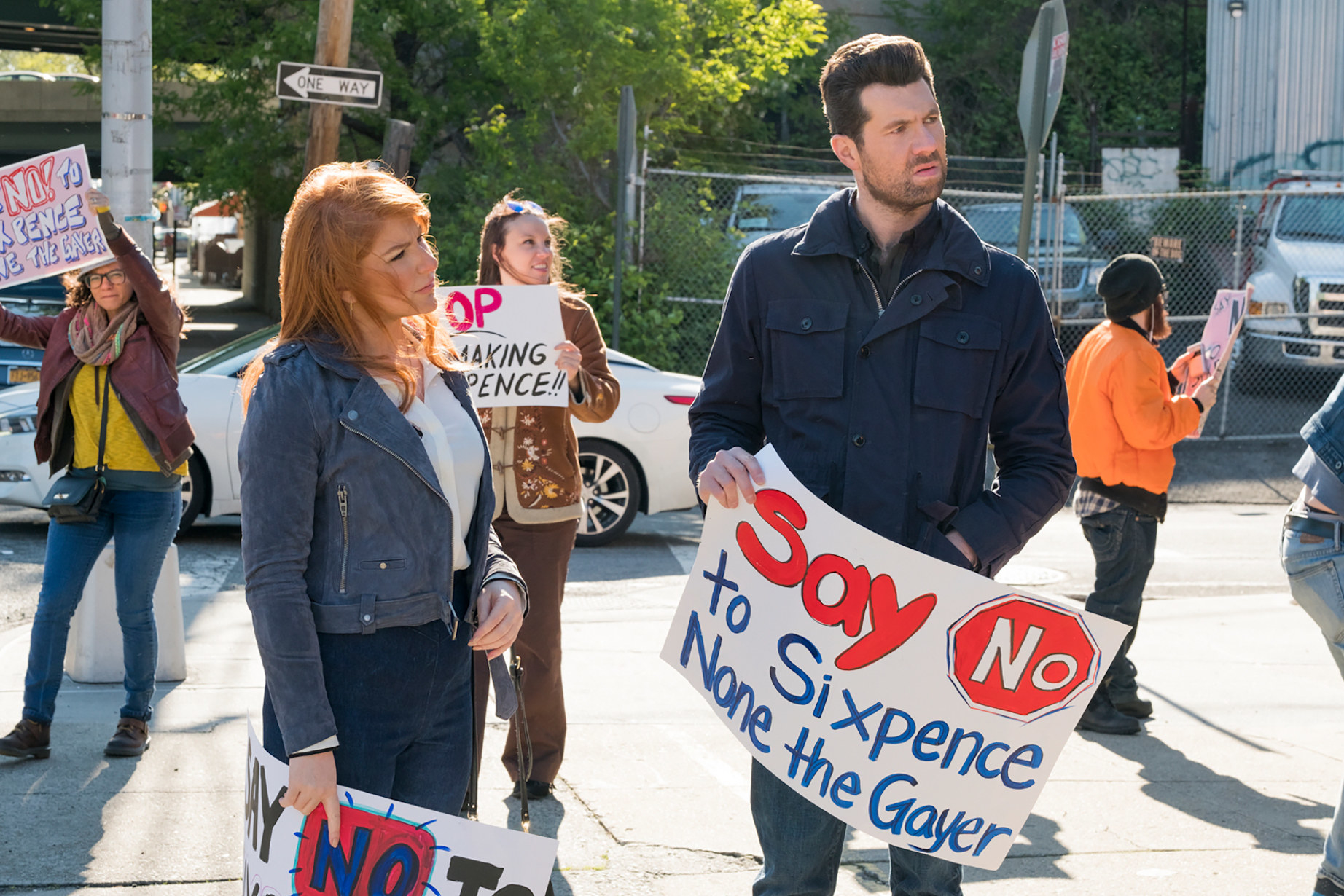 Julie Klausner and Billy Eichner carrying signs, from 'Strike Rat' (Season 3, ep 302