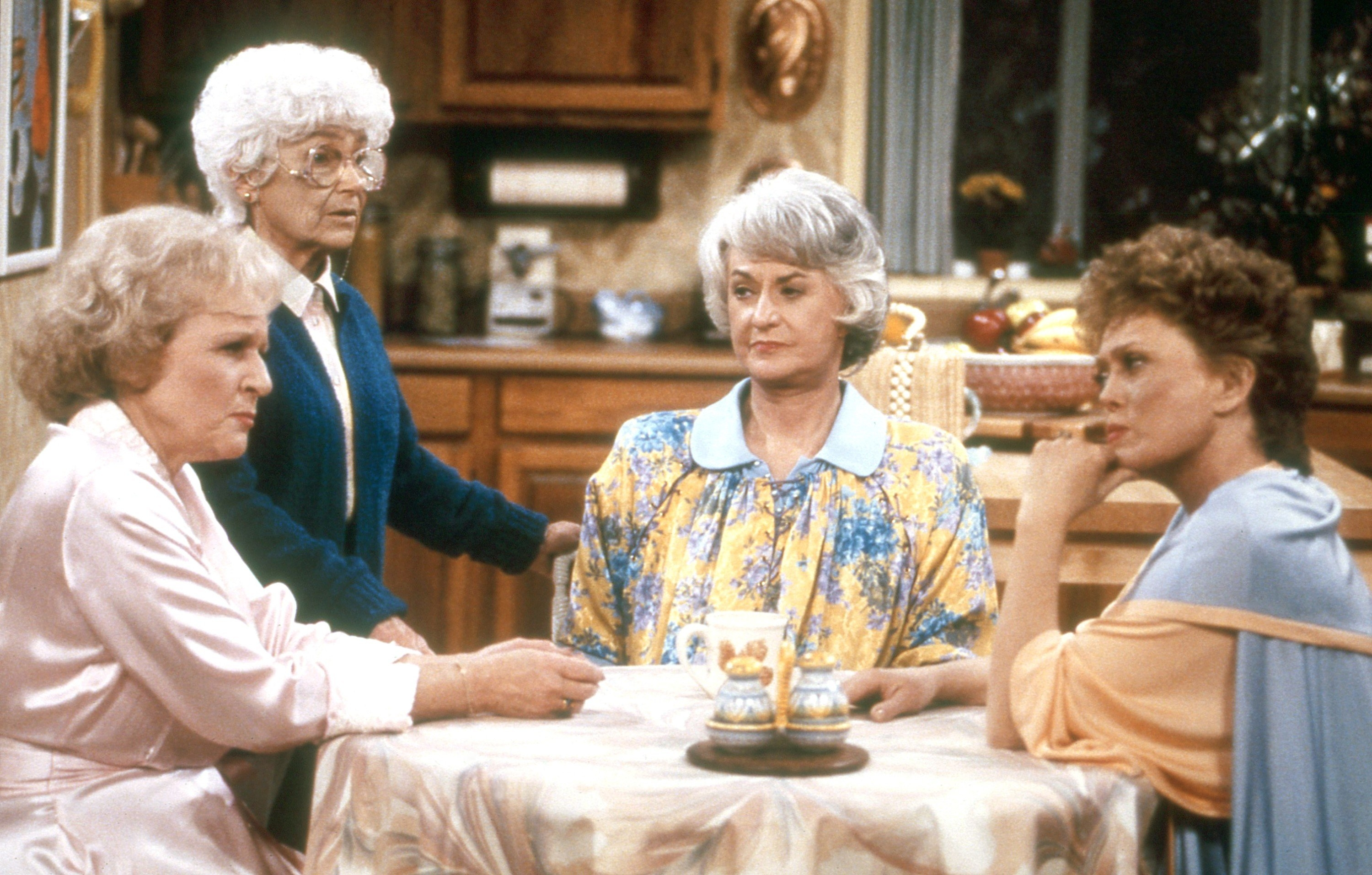 Betty White, Estelle Getty, Bea Arthur, and Rue McClanahan around a table in the kitchen