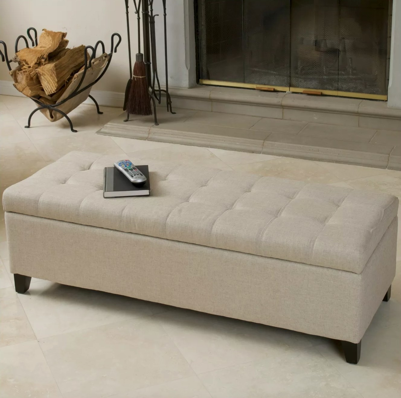 The tufted storage ottoman in beige near a fireplace