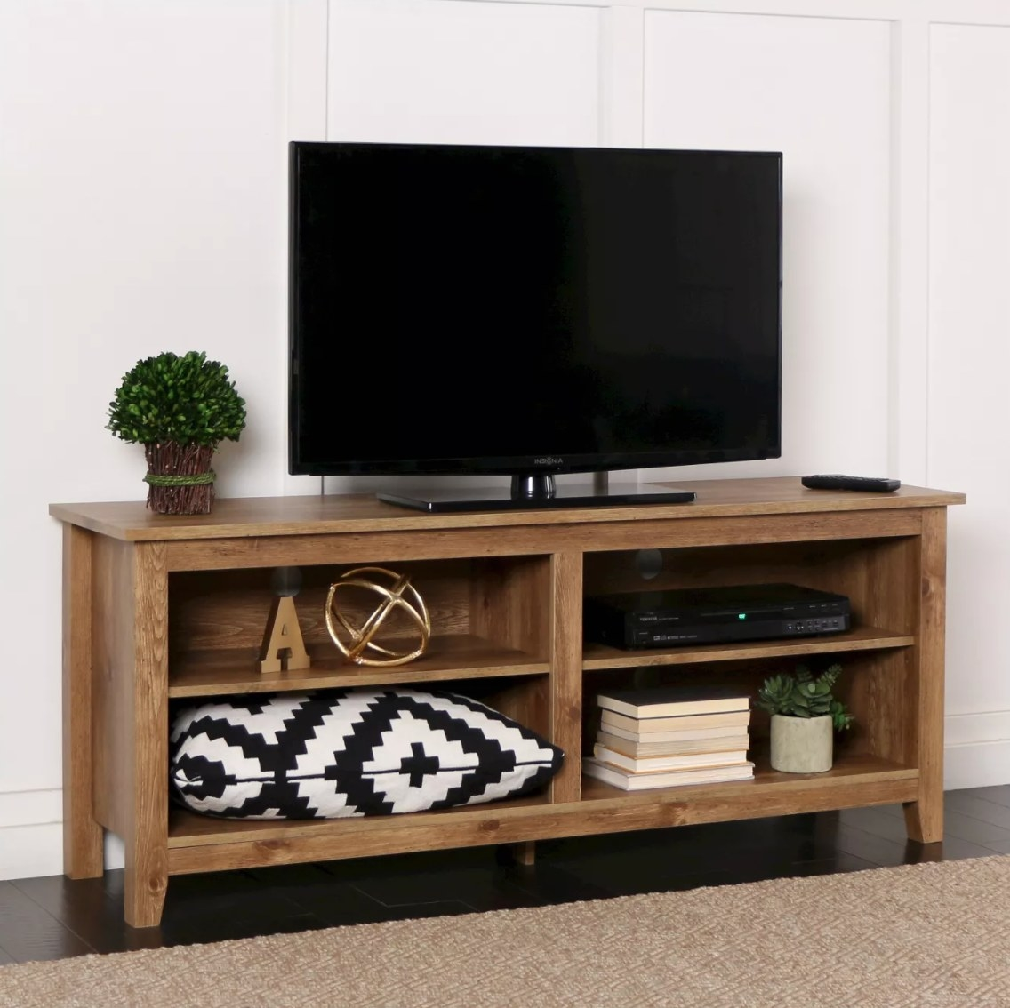 The rustic wood TV stand holding a flat-screen, pillows, books, and plants