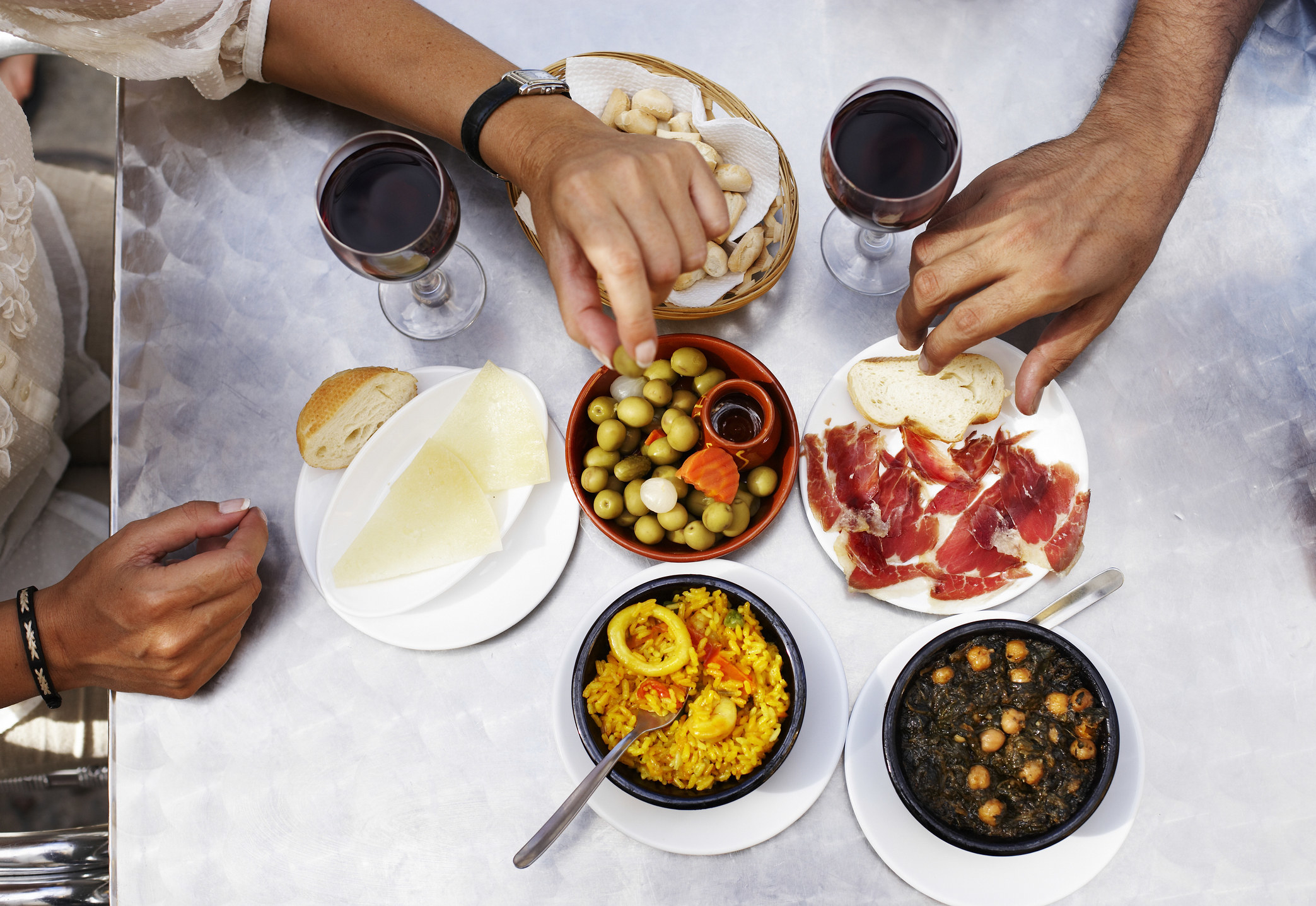A tapas meal with two glasses of wine.