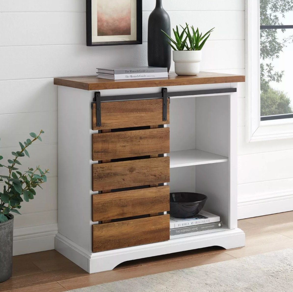 The rustic farmhouse cabinet holding books, bowls, and planters