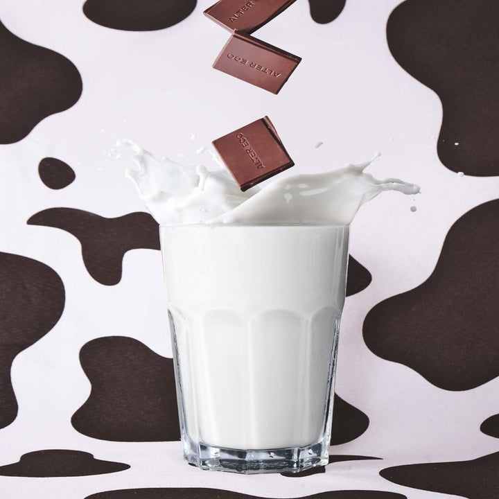 squares of chocolate fall into glass of milk