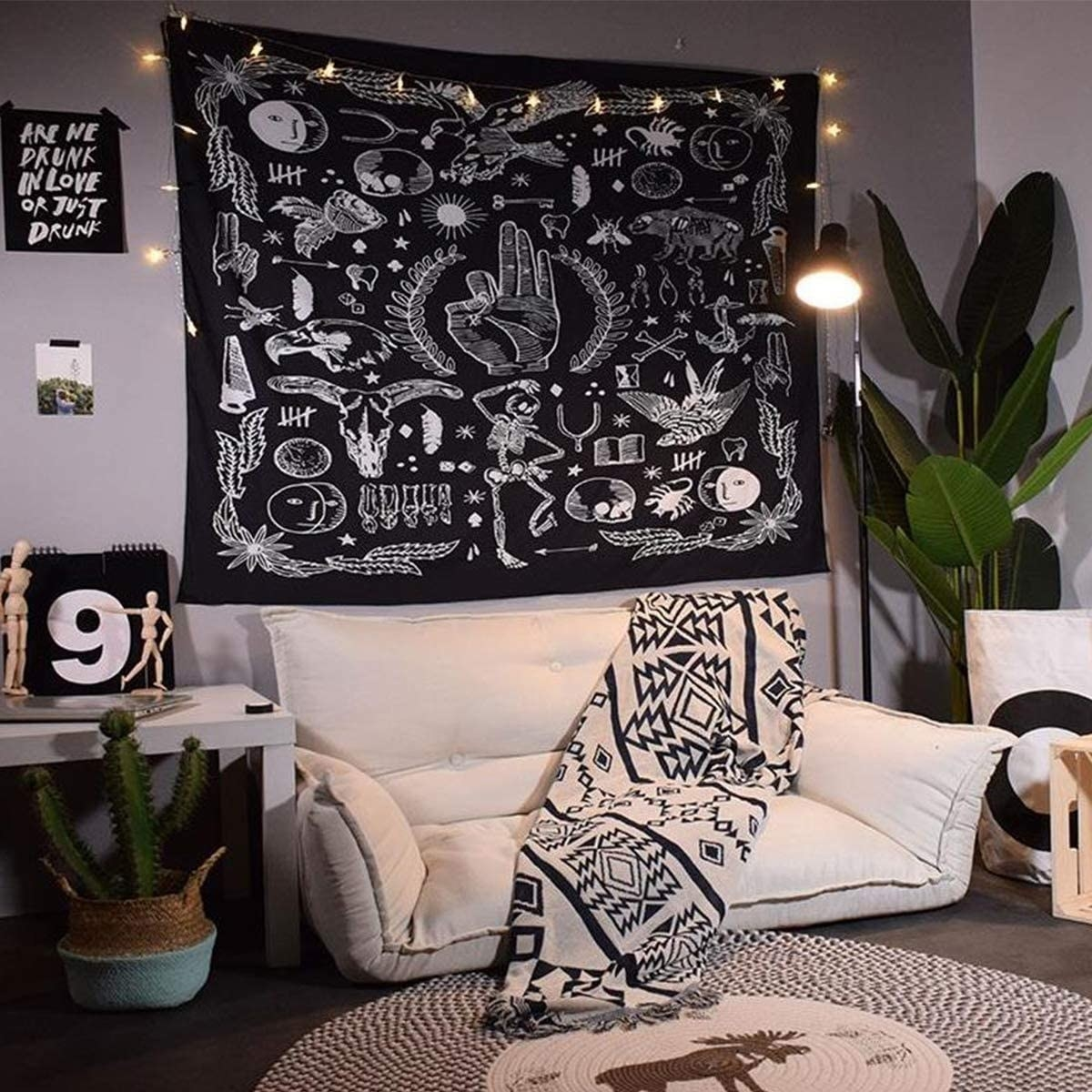 living room couch with black and white tapestry hung up on the wall featuring skulls and other gothic symbols