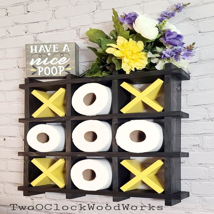 three by three box grid tic-tac-toe wall shelf, that comes with x's and uses toilet paper rolls for o's