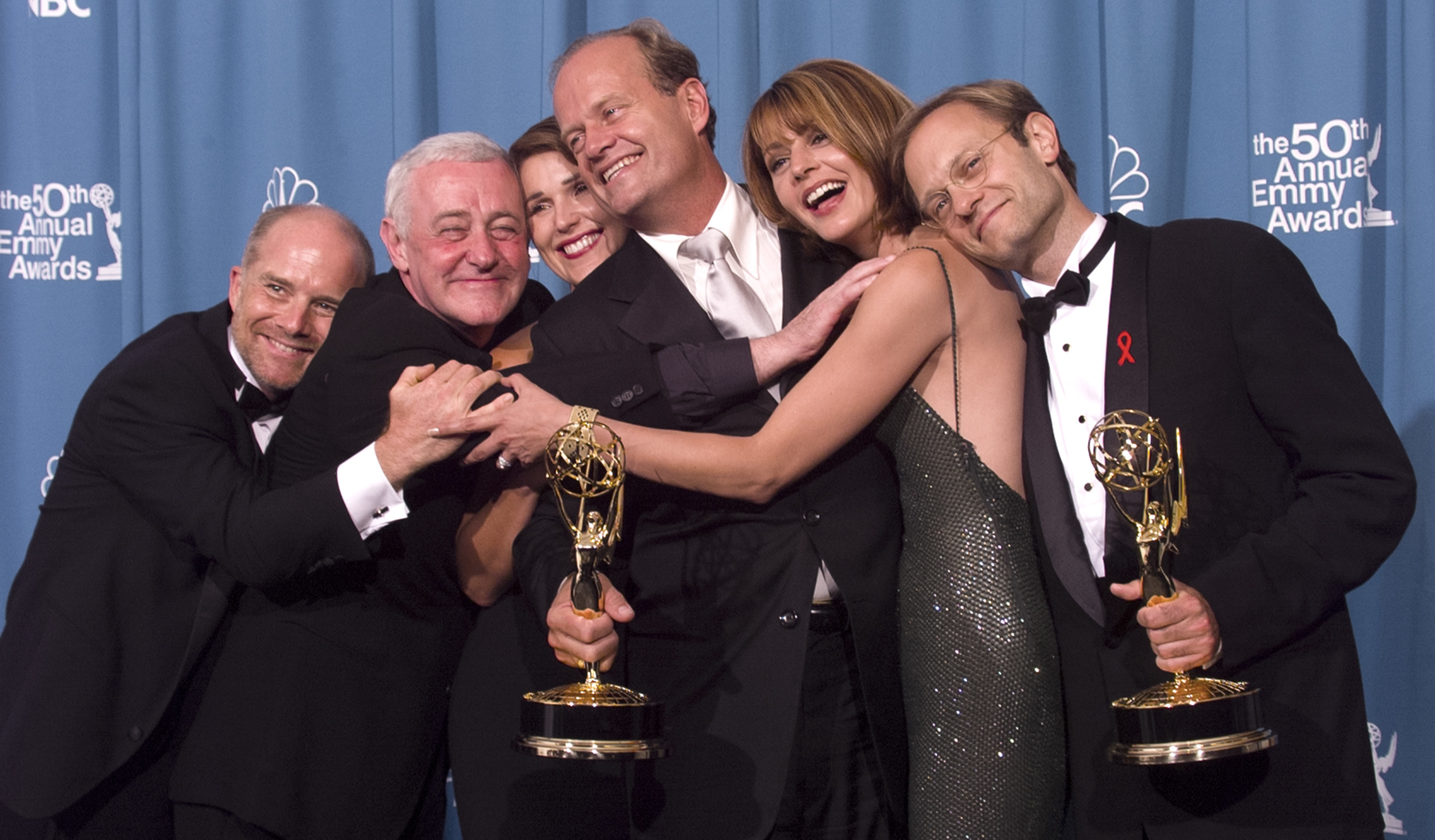 """The cast of """"Frasier"""" embracing while holding two Emmy Awards"""