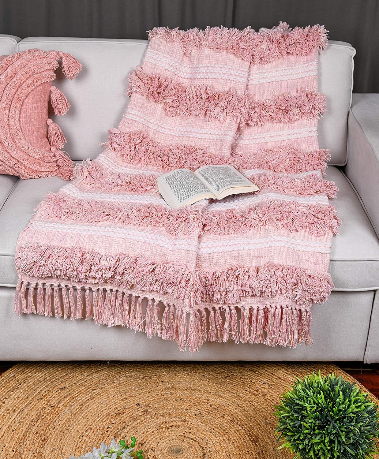 A baby pink throw with alternating rows of cloth and tassel.
