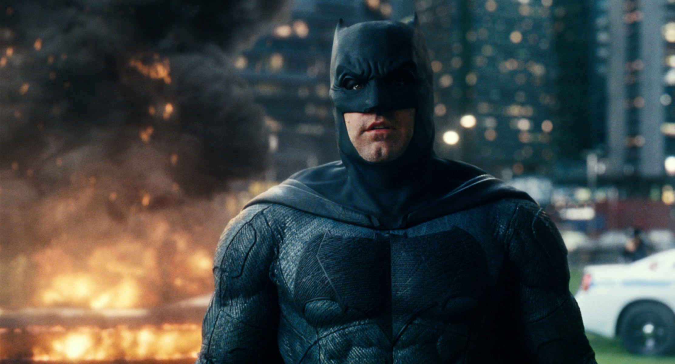 Photo of Ben Affleck dressed as Batman with an explosion behind him