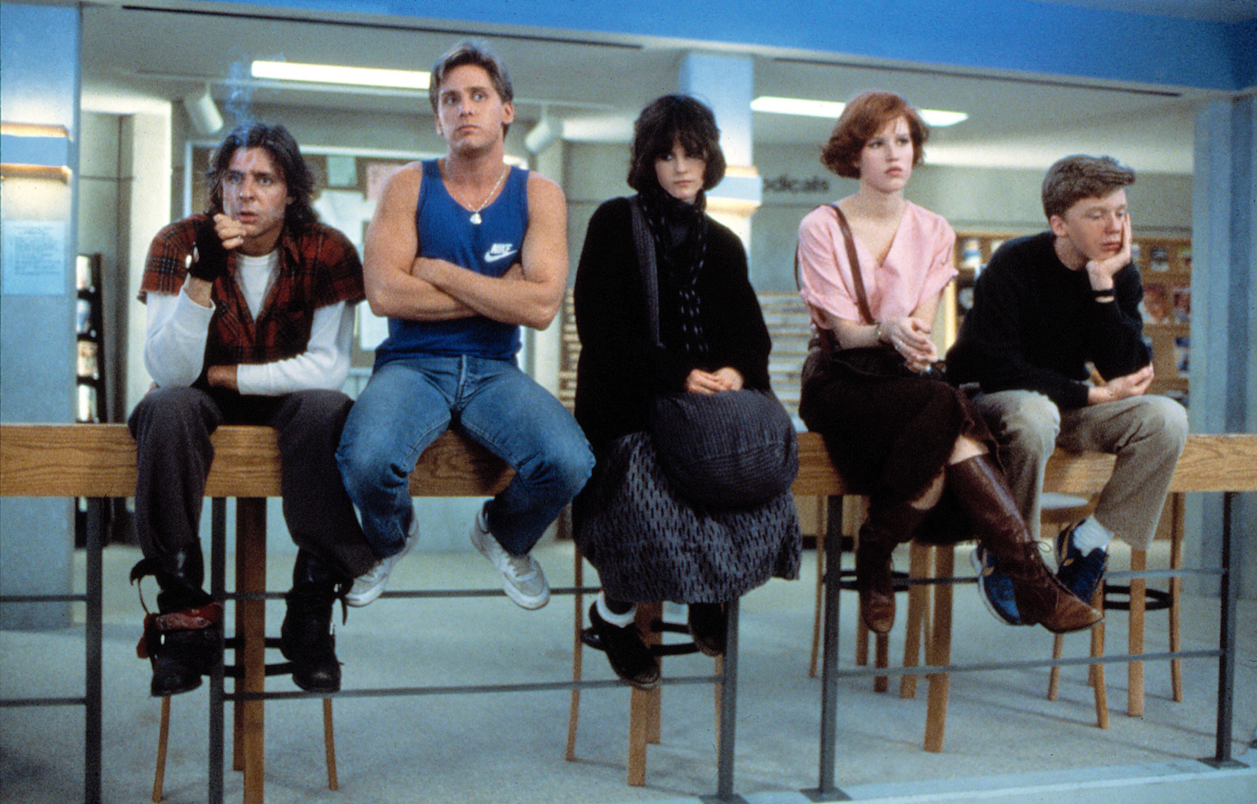 Photo of Breakfast Club cast sitting on a handrail in the library