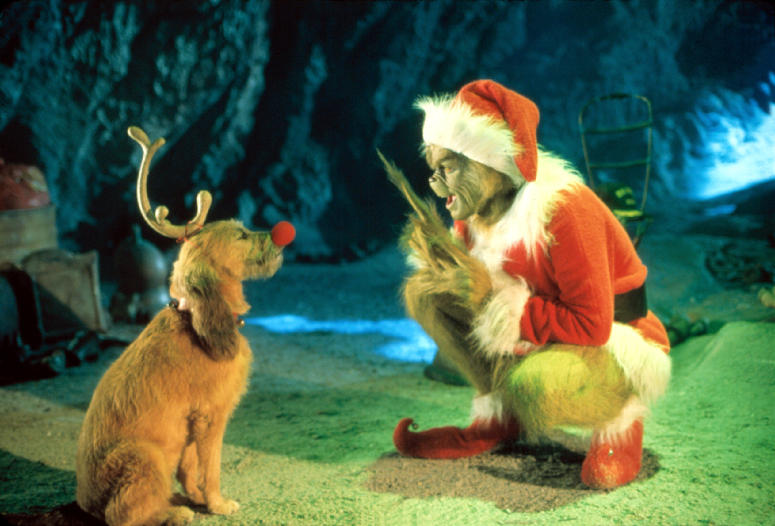 Photo of the Grinch dressed as Santa talking to his dog