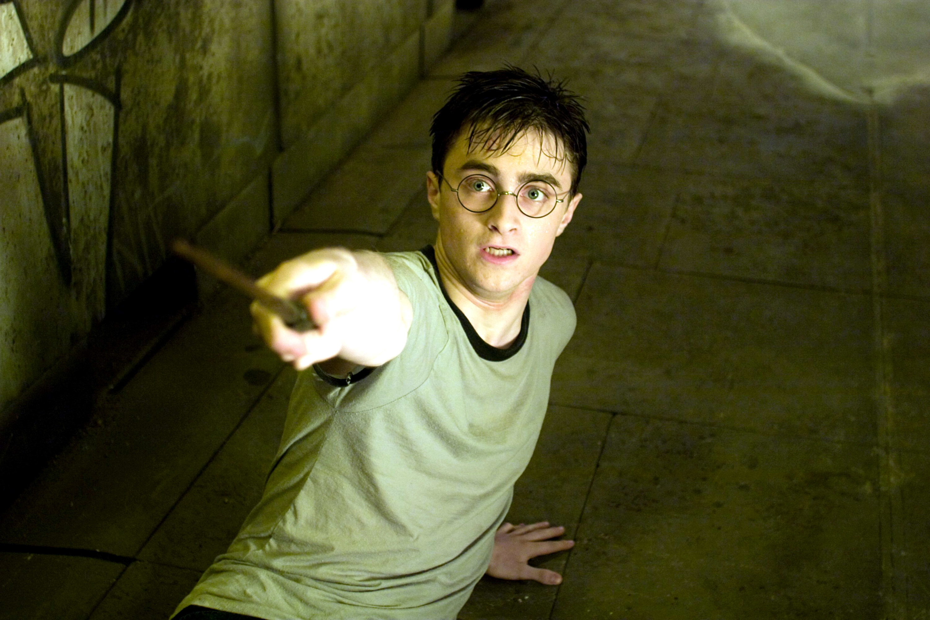 Photo of Harry Potter on the ground looking scared and pointing his wand