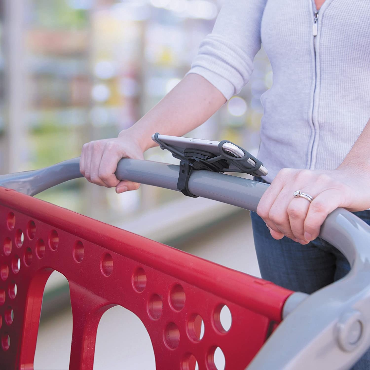 A person pushing a shopping cart with the phone mount attached to it