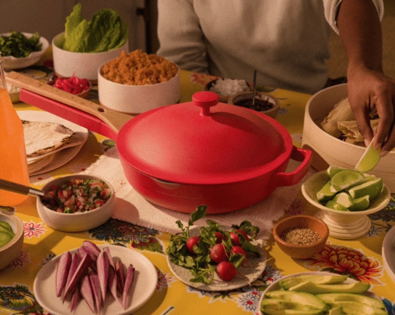 """The """"Heat"""" pan surrounded by fruits and veggies on a table with a yellow cloth"""