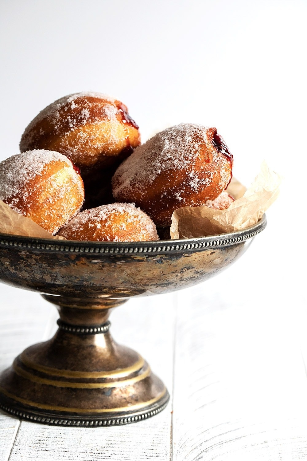Metal bowl filled with powdered filled donuts