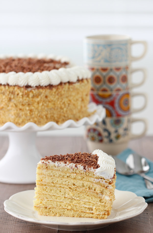 A high, layered yellow cake topped with brown flakes and a white cream