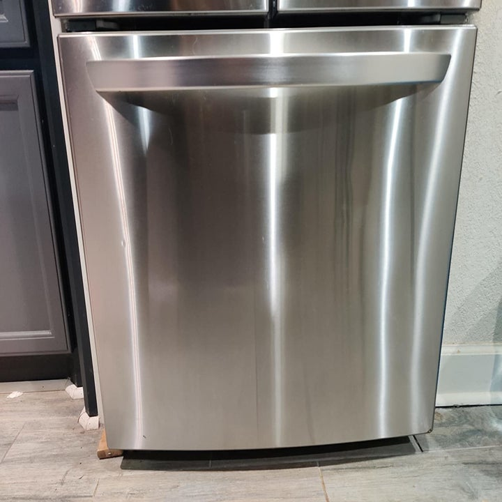 reviewer image of the same stainless steel freezer door streak-free after using the stainless steel wipes