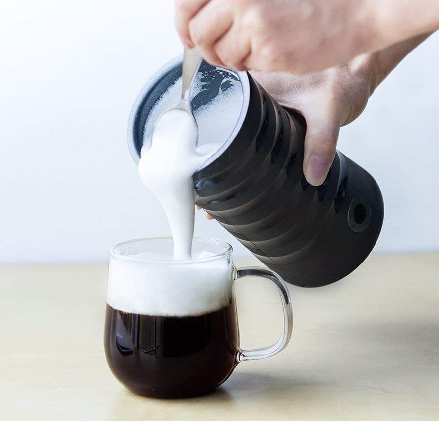 Someone pouring the milk froth into their coffee cup