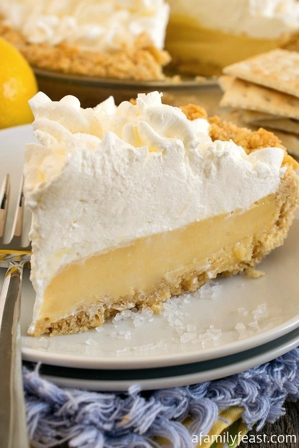 Lemon custard pie topped with a thick layer of cream