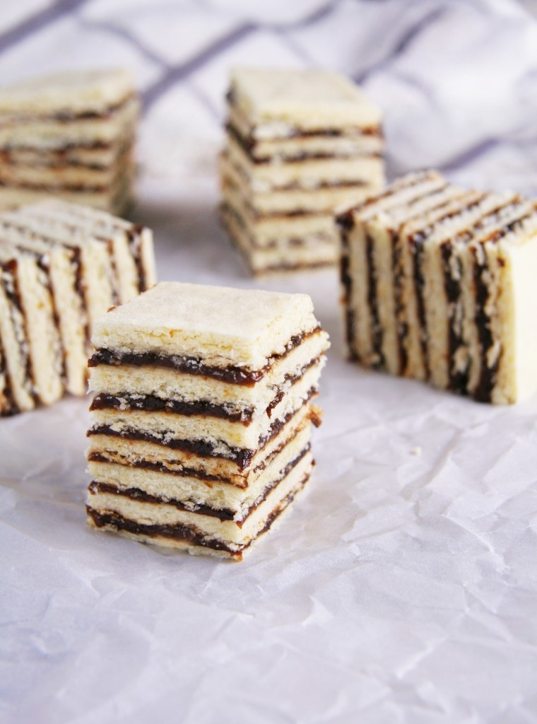 Cakes layered with jam, cut into squares, and laying on white parchment paper