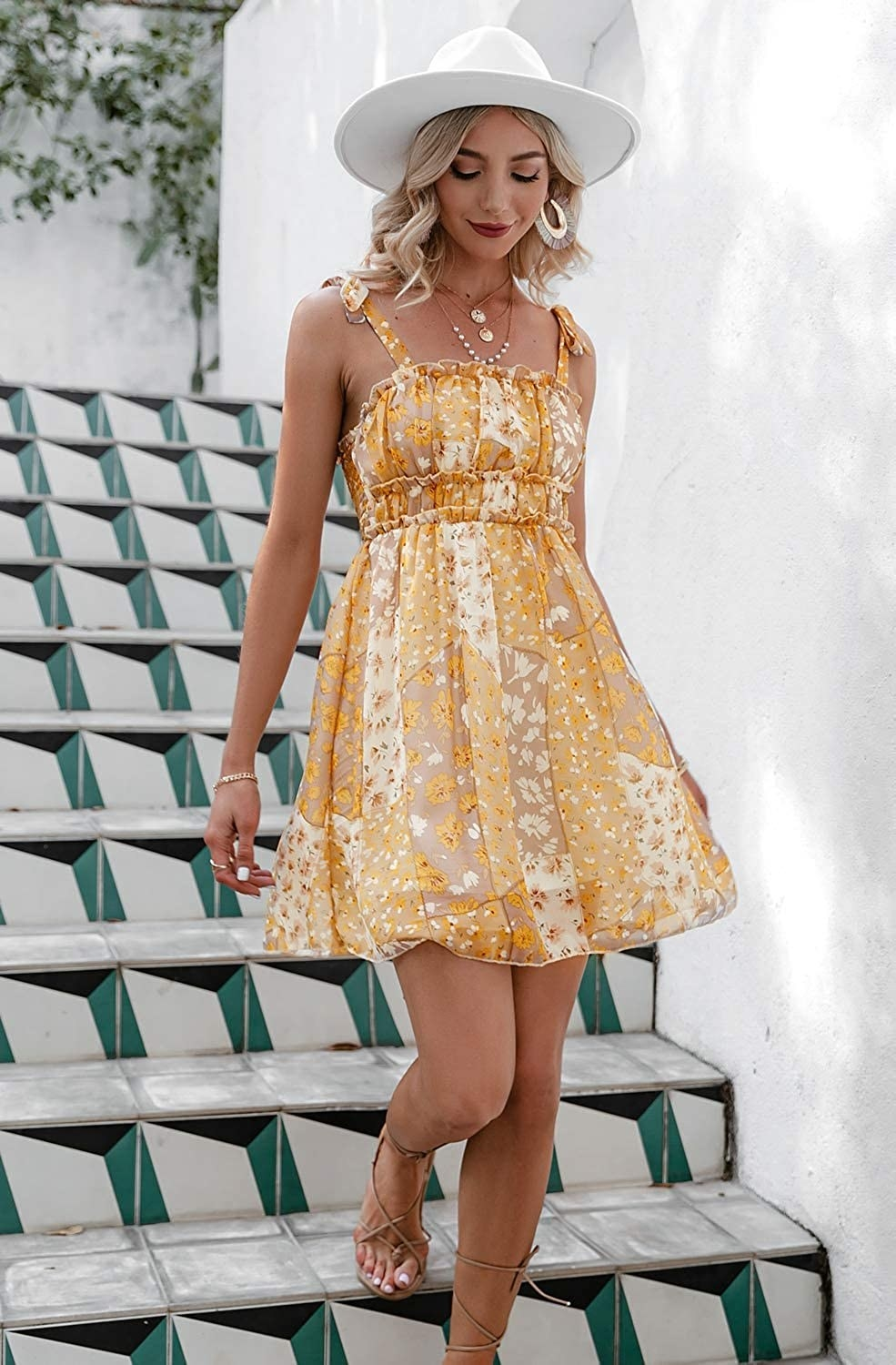 A model wearing the dress in B-yellow while walking down some stairs