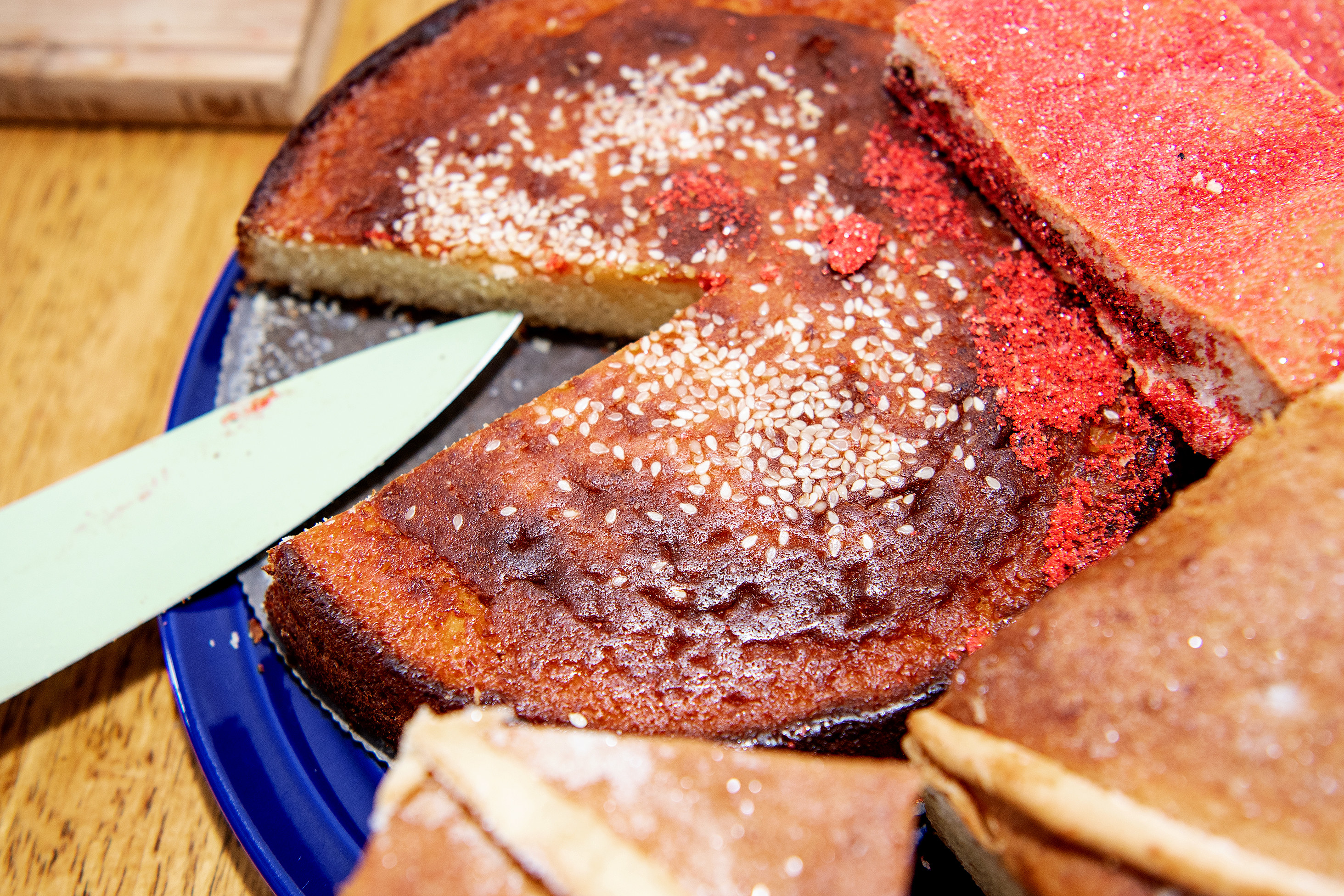 Knife cutting into Salvadoran quesadilla, or cheese pound cake. Other El Salvadorean treats surround the cake.