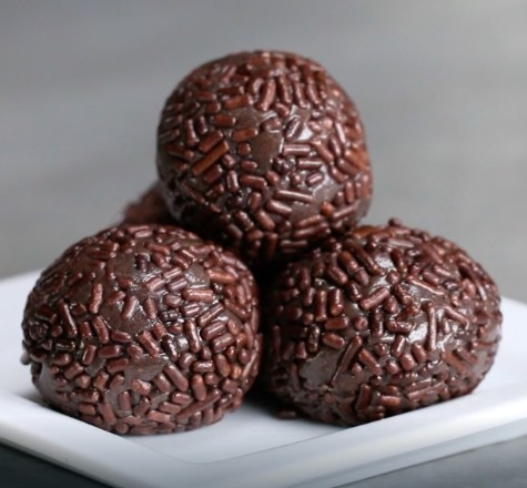Dark chocolate truffles covered with sprinkles stacked on a white plate