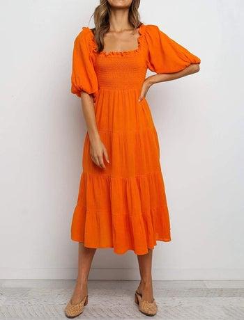 A model wearing the dress in orange