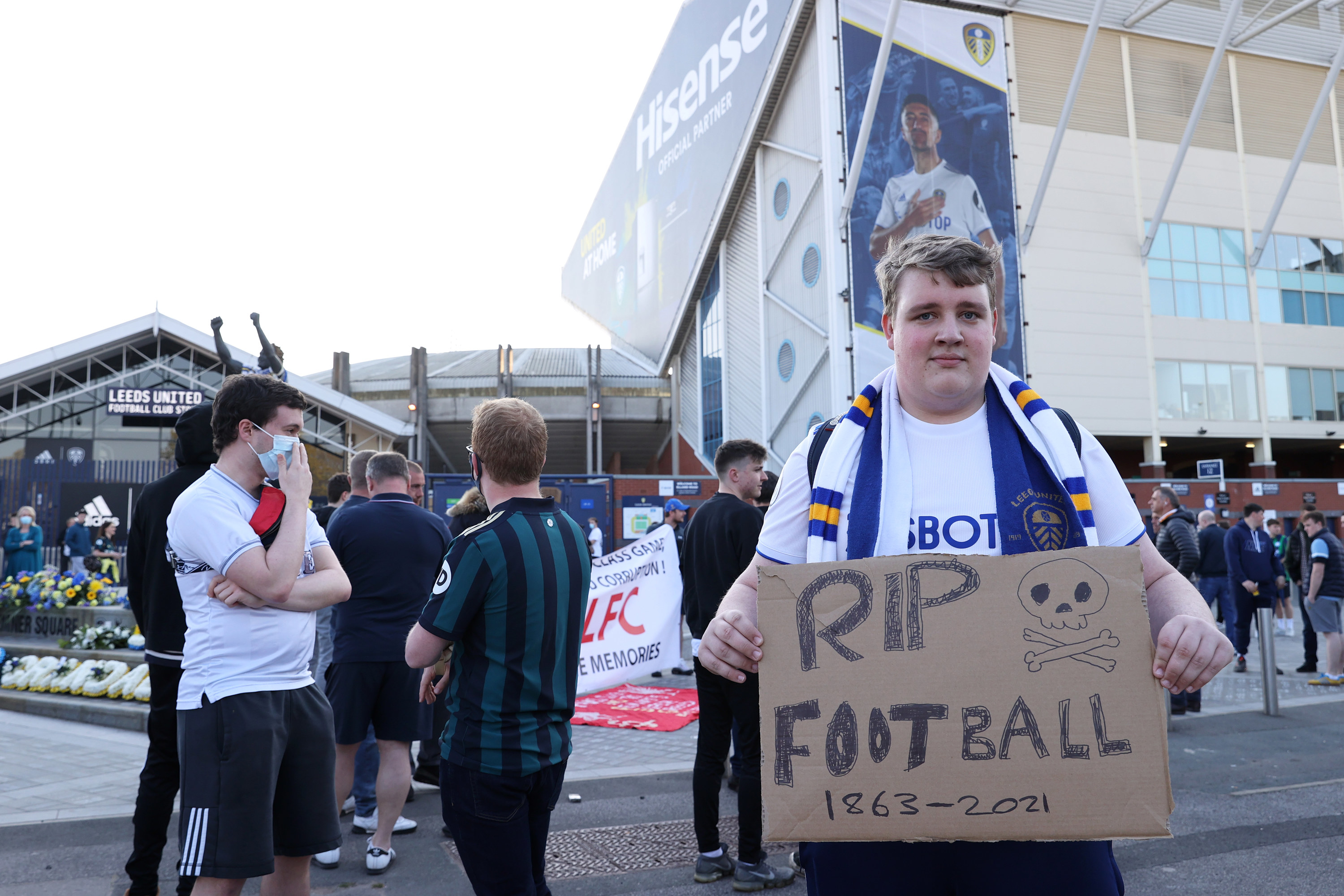 """Leeds fan holding a cardboard sign that says, """"RIP Football 1863–2021"""""""