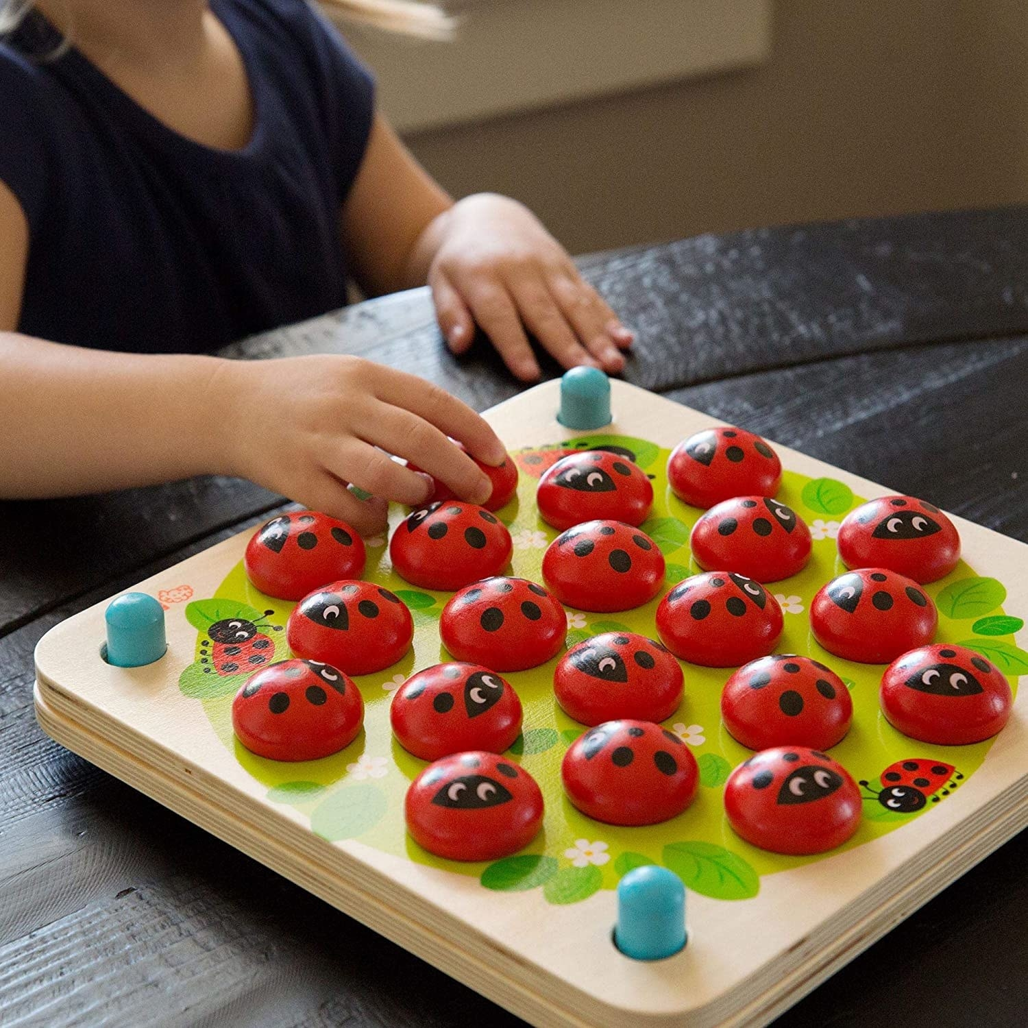Close-up of a child's hands as they flip over the ladybug piece