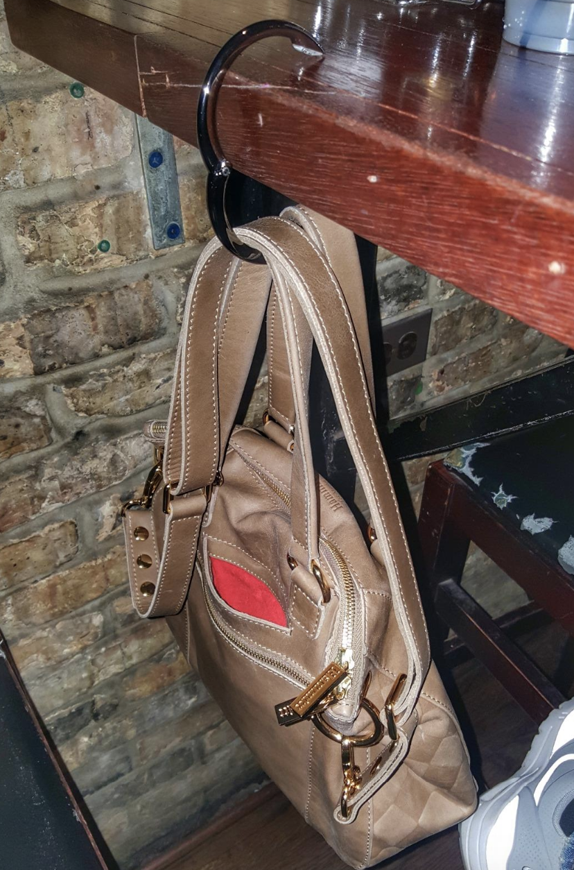 reviewer's purse hanging from table at restaurant using the clip