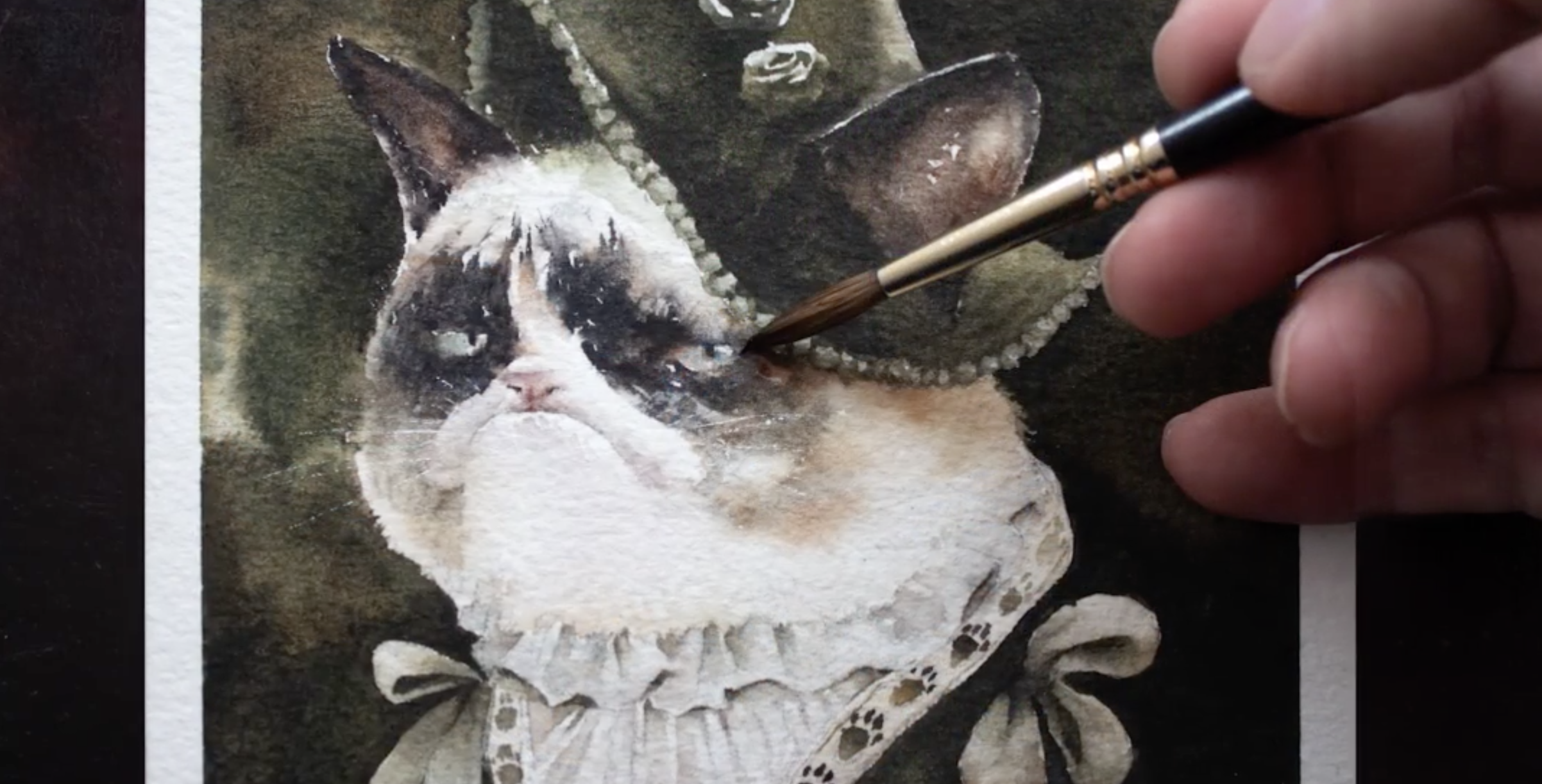 person painting a cat with watercolours