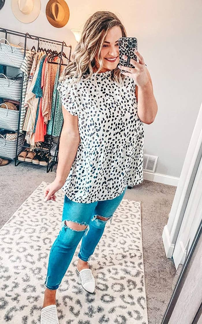 Person is wearing a white and black dotted tunic and denim jeans