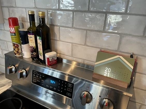 Reviewer's picture of their olive oil bottles and more stored on the stove's magnetic strip