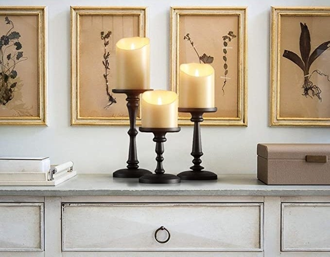 a set of three matte black candle holders holding lit candles