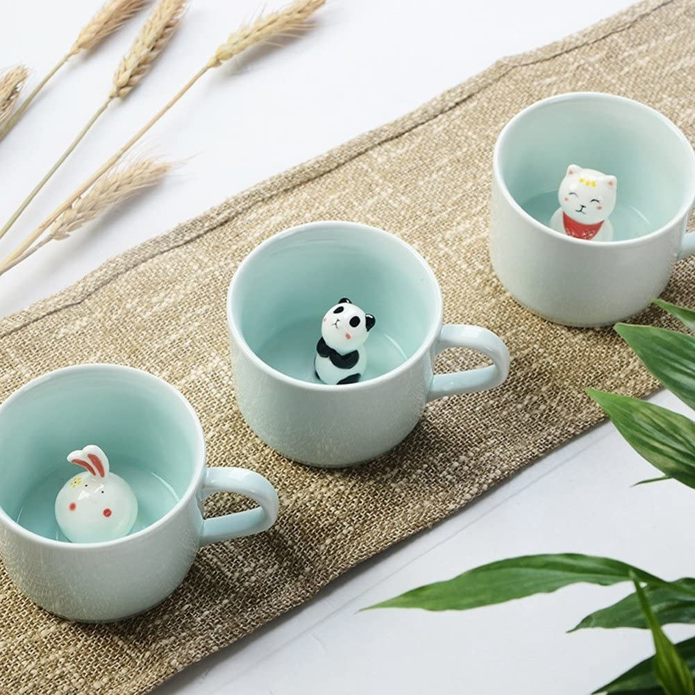 three of the mug on a table with the panda one in the middle