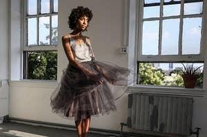 A model wearing the dark gray knee-length skirt