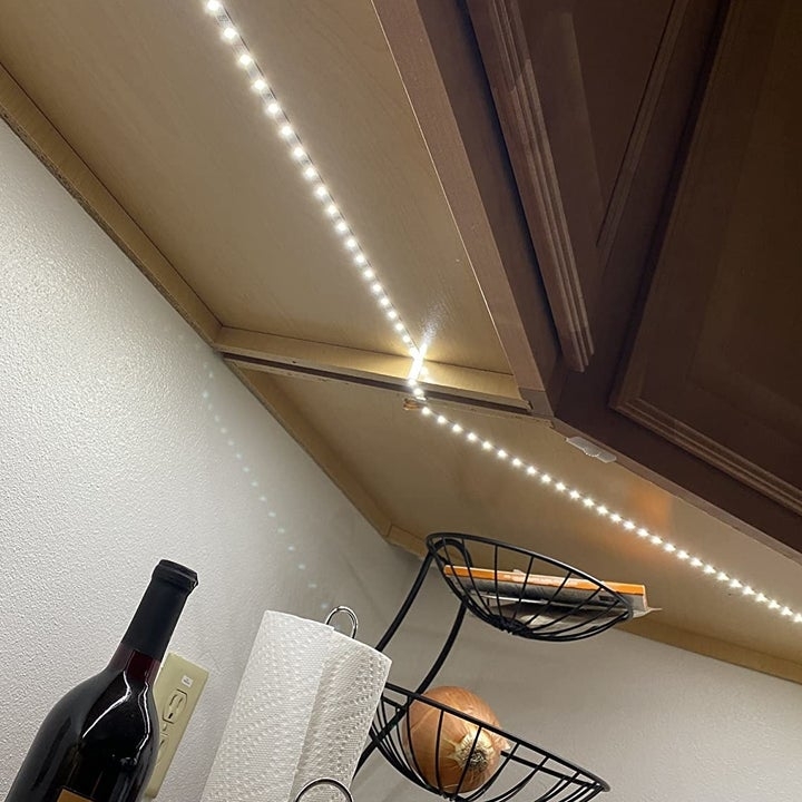 a reviewer photo of a cabinet with light atrips installed underneath