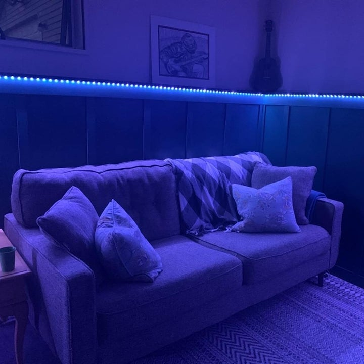 a reviewer photo of a darkened room with a strip of blue lights along the molding